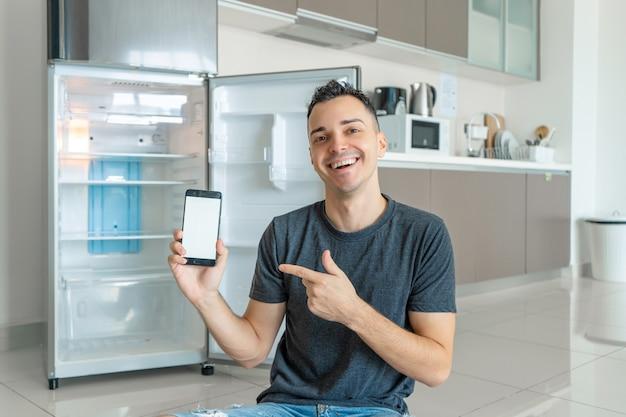 Guy commande de la nourriture à l'aide d'un smartphone près d'un réfrigérateur vide