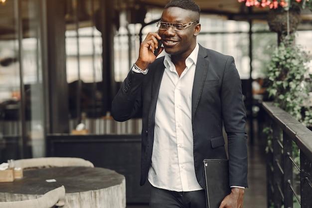 Guy en costume noir. homme avec un téléphone portable. homme d'affaires au bureau.