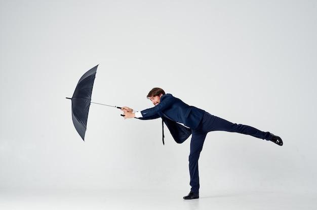 Guy en costume avec un parapluie à la main sur un fond clair par temps venteux