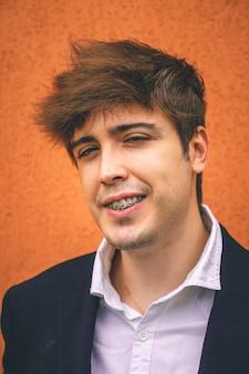 Guy en costume souriant sur un mur orange