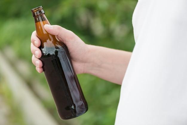 Guy crop avec de la bière dans la nature