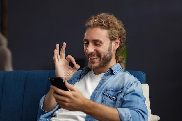 Guy curvy à l'aide de smartphone et souriant. homme heureux utilisant des applications de téléphonie mobile, sms, navigation sur internet, regardant un smartphone, assis à la maison. les jeunes travaillant avec des appareils mobiles.