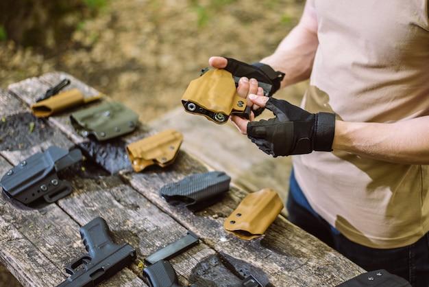 Guy dans les bois teste ses armes pour le tir sportif