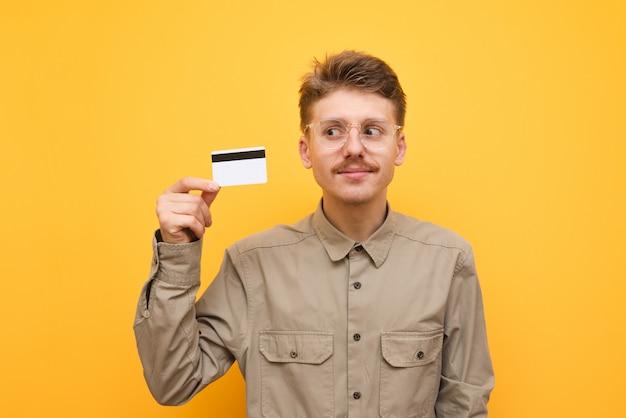 Guy dans la chemise et les lunettes tient une carte de crédit à la main.