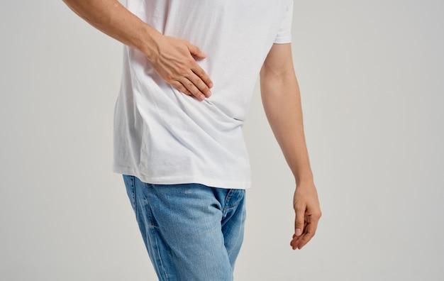 Guy dans un t-shirt et un jean touche ses mains près de la douleur abdominale problèmes d'estomac appendicite. photo de haute qualité
