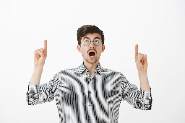 Guy debout encore inquiétant plafond va tomber. homme intelligent créatif intéressé avec barbe et moustache, pointant et levant la mâchoire tombée, voyant quelque chose de curieux sur un mur gris