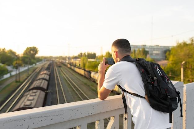 Guy debout sur le pont photographie les voies ferrées