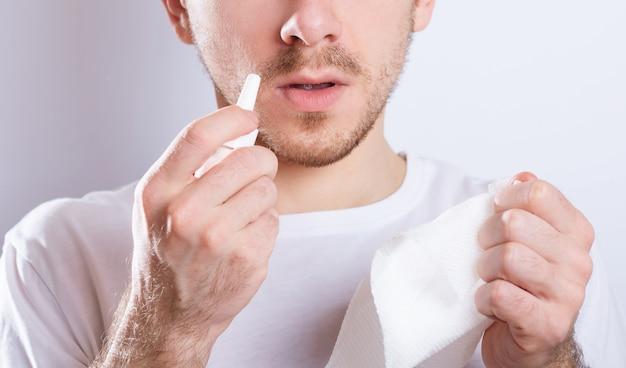 Guy dégoulinant de gouttes nasales dans le nez, portrait, gros plan