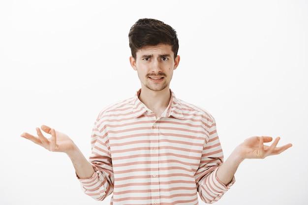 Guy écoutant des explications ridicules, sans aucune idée ni impression. séduisant frère caucasien avec moustache et barbe, paume étendue et haussant les épaules, fronçant les sourcils de malentendu, inconscient