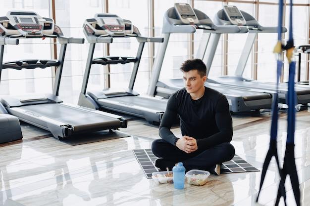 Guy élégant dans la salle de gym se détendre sur le sol et manger des aliments sains.