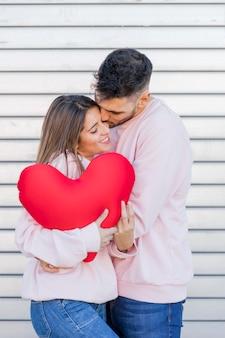 Guy embrasser femme tenant jouet symbole du coeur