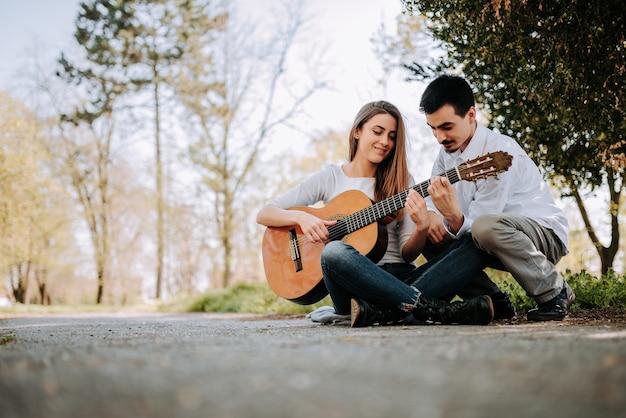 Guy enseignement fille à jouer de la guitare dans le parc.