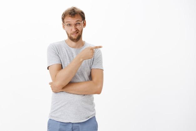 Guy essayant d'exprimer son aversion en pointant poliment vers la droite en plissant les yeux et en grimaçant de mécontentement ne pas être impressionné par le faible travail de l'équipe debout mécontent et douteux