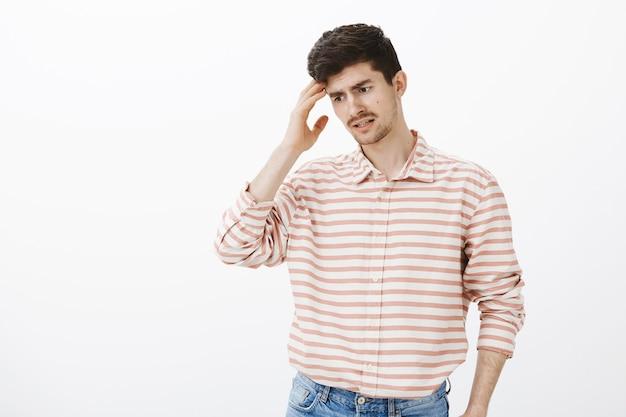 Guy essayant de se rappeler ce qu'il a oublié. portrait d'homme séduisant confus oublieux avec barbe et moustache, regardant vers le bas et tenant la paume sur la tempe, se sentant nerveux en pensant au mur gris