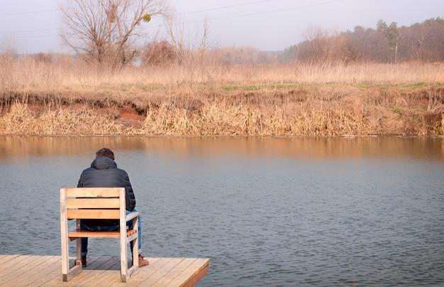 Guy est assis sur une chaise sur une jetée en bois et regarde la rivière. le concept d'intimité et de tranquillité en silence.