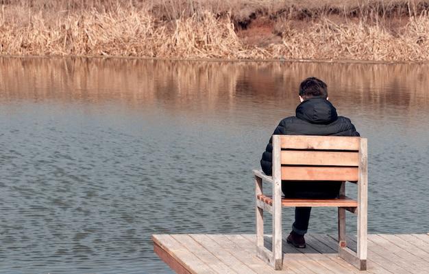 Guy est assis sur une chaise et regarde la rivière. le concept d'intimité et de tranquillité en silence.