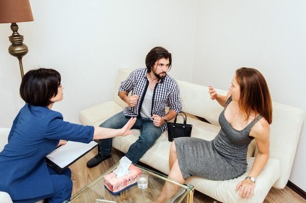 Guy est assis à côté de sa femme et tient les doigts dans le poing. il est prêt à la frapper. la jeune femme a peur de lui. elle se penche en arrière. elle atteint l'homme avec la main.