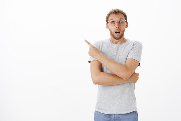 Guy étant ravi et surpris en ouvrant la bouche par surprise, regardant excité et pointant vers le coin supérieur gauche