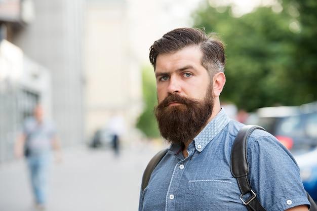 Guy explorant la ville. tourisme confortable. vacances d'été. hipster portant le fond de la rue urbaine sac à dos. homme barbu voyage avec sac à dos. concept touristique. sac à dos pour les déplacements urbains.