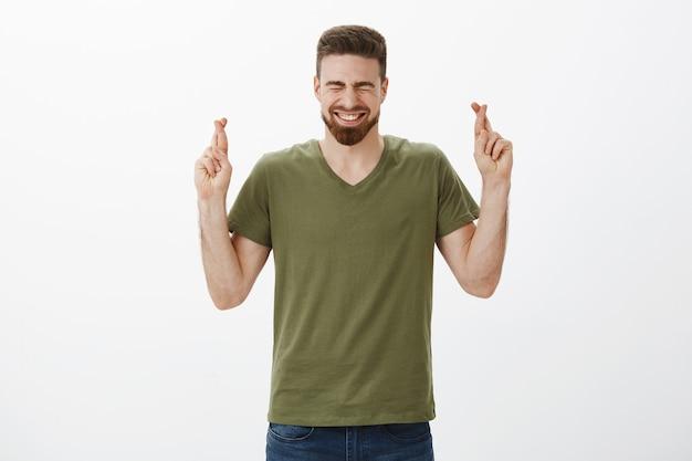 Guy faisant l'effort de prier souhaitant gagner en cas d'événement souriant fermer les yeux dans la joie et l'excitation croiser les doigts pour la bonne chance en voulant que le rêve se réalise, debout avec espoir sur le mur blanc