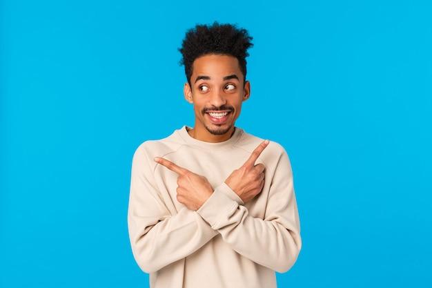 Guy faisant l'hypothèse de ce qu'il a pour les vacances. hipster afro-américain charmant mignon et excité