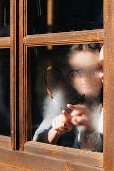 Guy et femme dans la maison, se détendre et dessiner un coeur sur une fenêtre