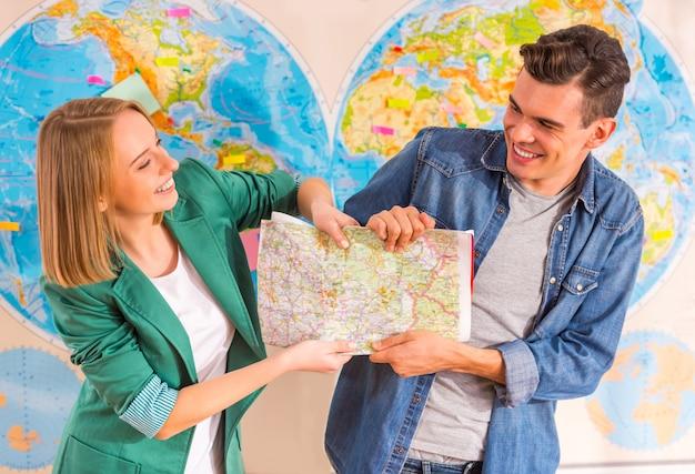 Guy et fille avec carte du monde tire la carte.