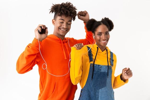 Guy et fille dans des vêtements colorés dansant tout en écoutant de la musique avec des écouteurs, isolé sur un mur blanc