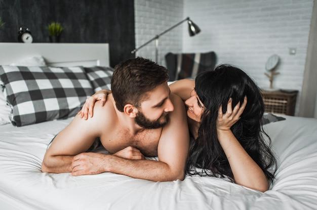 Guy et fille étreignant dans son lit. guy et fille ont des relations sexuelles. couple amoureux au lit. nuit de noces. faire l'amour. amoureux au lit. la relation entre un homme et une femme. sexe entre un homme et une femme