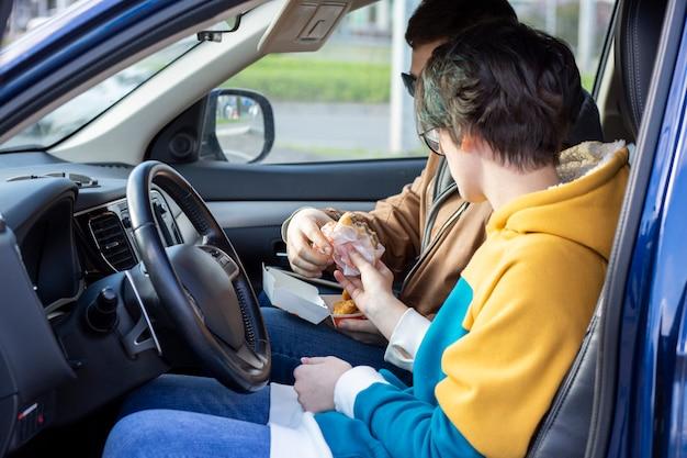 Guy et fille mangent des hamburgers et des pépites dans une voiture restauration rapide des aliments malsains