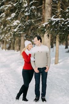 Guy et fille marchent, amusez-vous dans la forêt en hiver