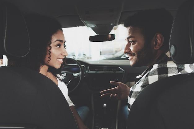 Guy et fille parlent à l'intérieur d'une voiture en choisissant un véhicule