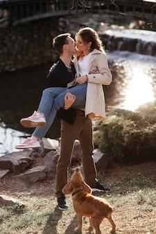 Guy et fille s'embrassant dans la rue près de leur chien