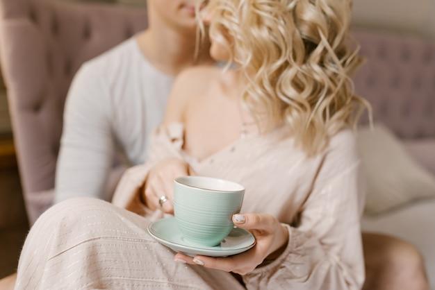 Guy et fille avec une tasse de café au lit, soft focus