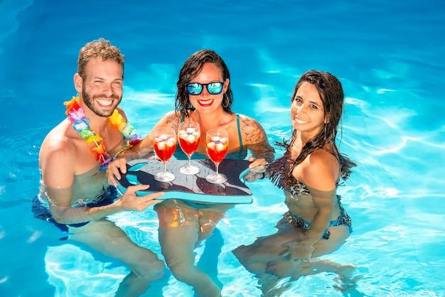 Guy flirtant avec deux femmes à la piscine, buvant dans une journée ensoleillée