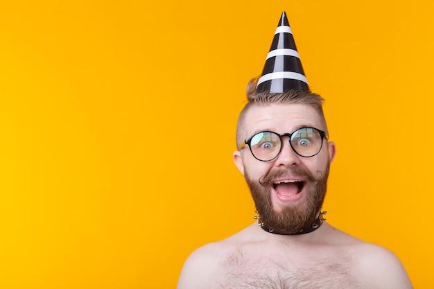 Guy hipster joyeux fou dans un bonnet de papier avec une moustache et une barbe criant de joie posant