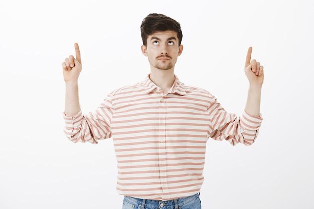 Guy immobile, inquiet des chutes de pierres. portrait d'un gars européen nerveux intense avec moustache, levant l'index, regardant et pointant vers le haut, s'intéressant à ce qui se passe vers le haut