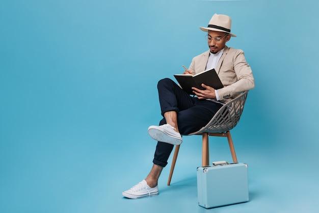 Guy in suit est assis sur une chaise et tient un livre