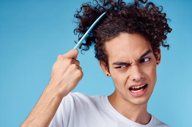 Guy indigné peigner les cheveux avec un peigne bleu sur fond isolé vue recadrée