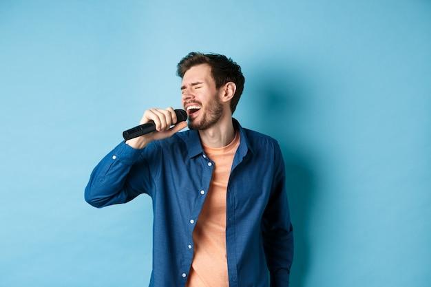 Guy insouciant chantant un karaoké avec microphone, interpréter une chanson, debout sur fond bleu. copier l'espace