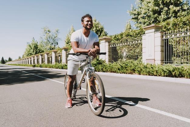 Guy latino est à bicyclette. route vide.