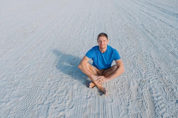 Guy marchant le long de la plage de sable vide de miami heureux bel homme touristique en vêtements décontractés assis sur la plage de sable