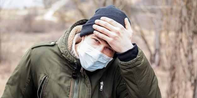 Guy en masque médical jetable tient son front avec sa main, vérifiant la température corporelle.