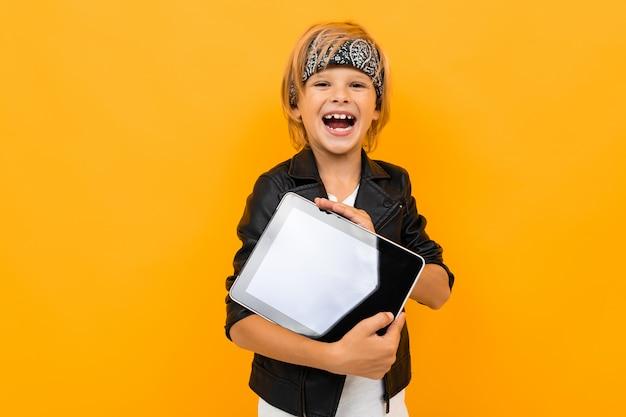 Guy à la mode avec un sourire rit avec une tablette dans ses mains