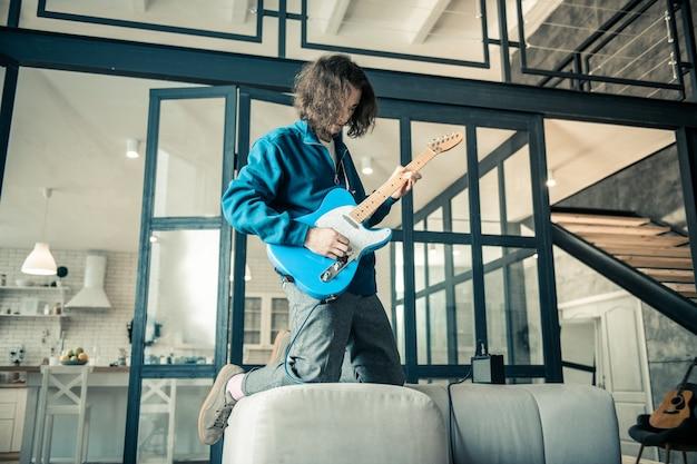 Guy montrant des compétences. musicien aux cheveux noirs téméraire exprimant ses sentiments tout en jouant sur un instrument de musique
