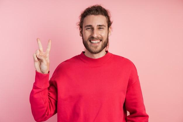 Guy montre le signe v, le signe de la victoire, de la paix. jeune homme positif.