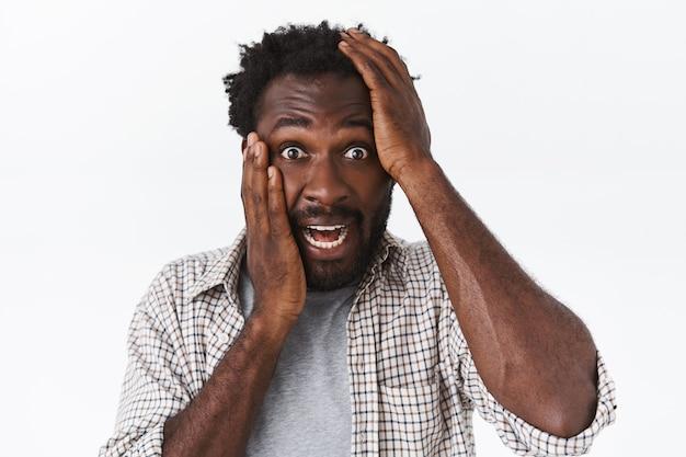Guy a peur, regarde avec panique et choc, le visage touchant ne peut pas se reconnaître