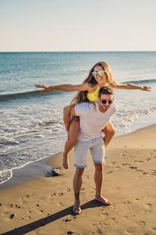 Guy portant une petite amie au rivage