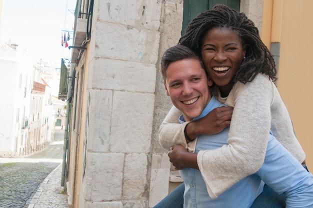 Guy portant une petite amie heureuse à son retour en ville
