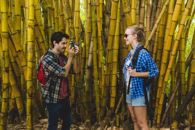 Guy prend une photo de petite amie dans une forêt de bambous